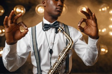 African smiling jazz performer with saxophone shows OK sign on the stage with spotlights