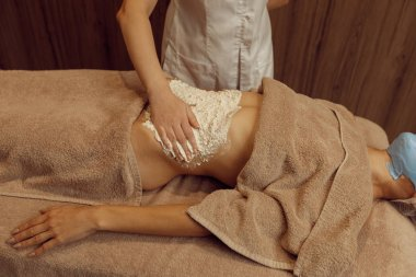 Female masseur rubbing cream on stomach of young slim woman in towel, professional massage. Massaging and relaxation, body and skin care. Attractive lady in spa salon