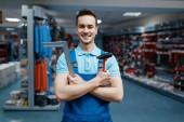 Mosolygó férfi munkás egyenruhában tartja kalapács és sarok szerszám boltban. Professzionális berendezések kiválasztása vaskereskedésben, műszerboltban