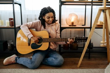Woman sitting on the floor and play the guitar at home, closeup view. Pretty lady with musical instrument relax in the room, female music lover resting