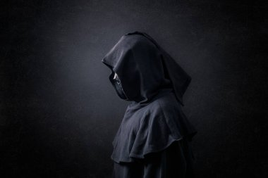 Scary figure in hooded cloak in the dark stock vector