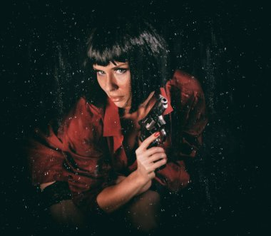 Beautiful woman with a revolver in her hands and raindrops flowing down the glass on black