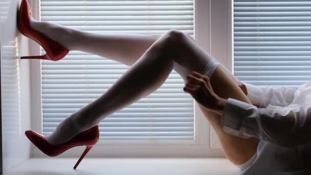 long female legs in white stockings and red high-heeled shoes on a window sill by the window with shutters