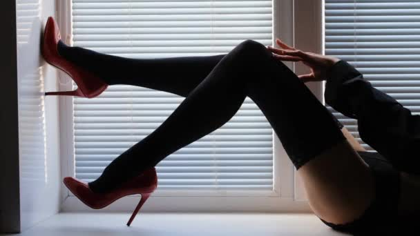 long female legs in black stockings and red high-heeled shoes on a window sill by the window with shutters