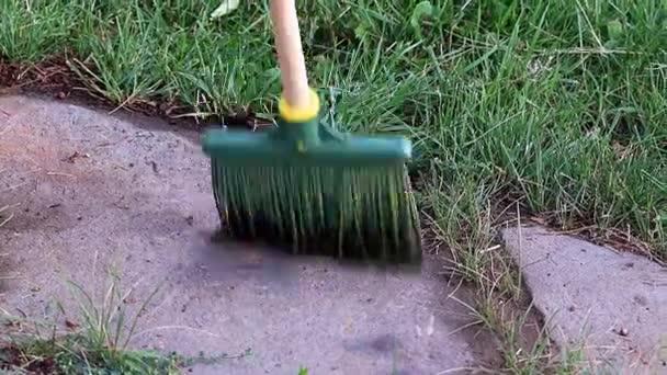 zametání odpadků s koštětem na zahradní ulici