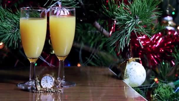 antike Uhr im Goldgehäuse und Gläser mit Saft auf dem Hintergrund eines Weihnachtsbaums