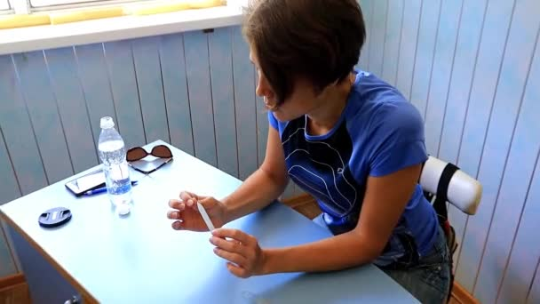 beautiful young woman handles finger nails with a tool, manicure