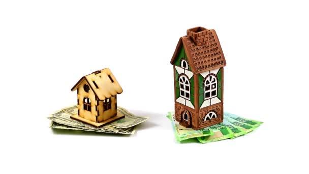 Dollarnoten und russische Rubel stehen neben einem Holz- und Keramikhaus