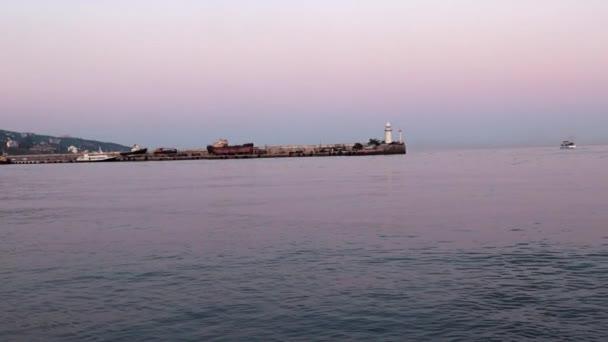 přístavní maják a jachtařské lodě večer
