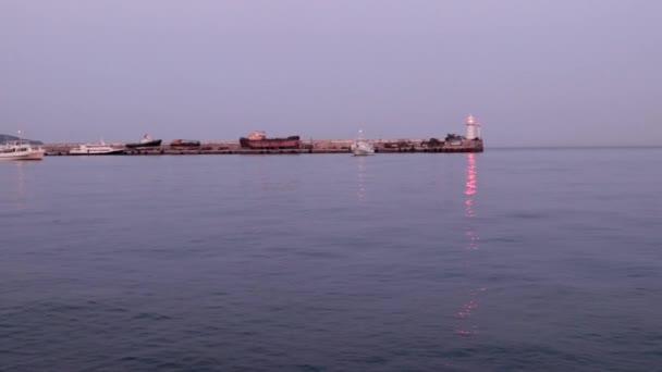 pohyb obchodní lodi a blikajícího majáku na molu ve vodní oblasti přístavu