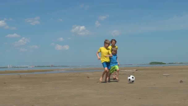 Kids playing soccer on a beach slow motion