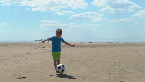 Children playing soccer on the beach at sunny day slow motion. Lifestyle, vacation, happiness, joy concept