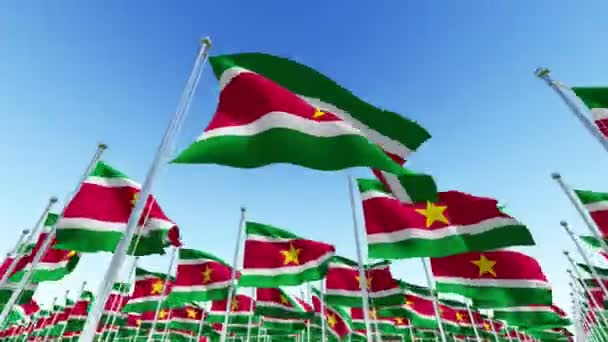 Many flags of Suriname fluttering in the wind on flag poles against blue sky.  Three dimensional rendering animation.