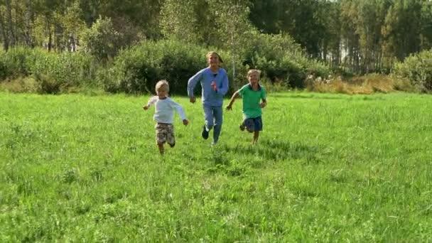 drei Jungen laufen an einem sonnigen Sommertag in lässiger Kleidung in Zeitlupe durch den Park.