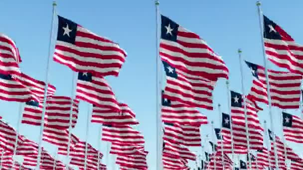 Many flags of Liberia waving in the wind on flag poles in a rows against blue sky.  Three dimensional rendering animation.