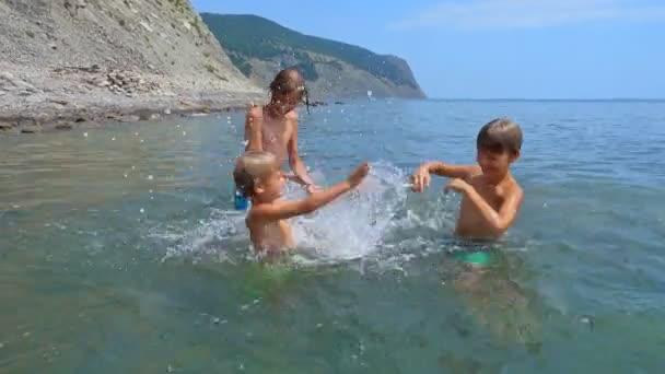 Šťastné děti hrají v moři. Děti baví venku. Letní prázdniny a koncept zdravého životního stylu
