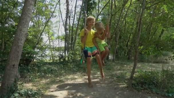 Šťastné děti chlapci smát a houpání na houpačce v letním dni