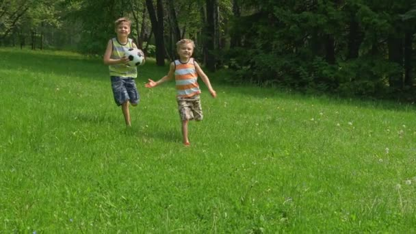 happy kids running with a soccer ball on green grass in sunny day. Slow motion.