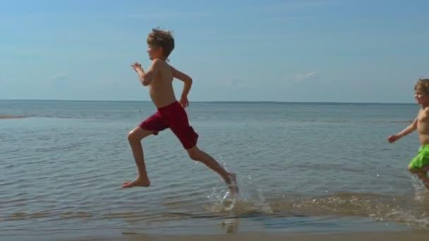 Glückliche Kinder rennen nacheinander am Sandstrand entlang
