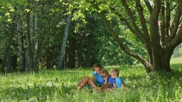 Tři kluci sedí na zelené trávě na zahradě. Děti, které čtení knihy pod stromeček, vzdělávají