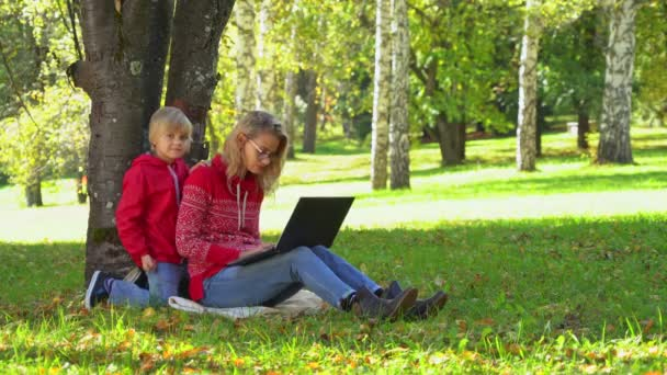 Young mother working on a laptop together with her child on a autumn background with fallen leaves and green grass.