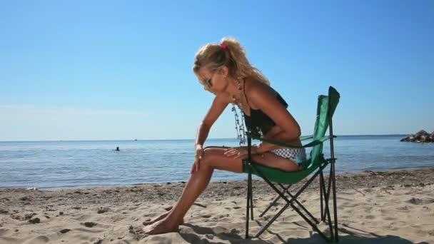 beautiful woman sitting on the beach and putting on sun screen