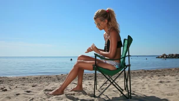 Young woman applying sunscreen lotion sitting on the chair at the beach, sunny weather