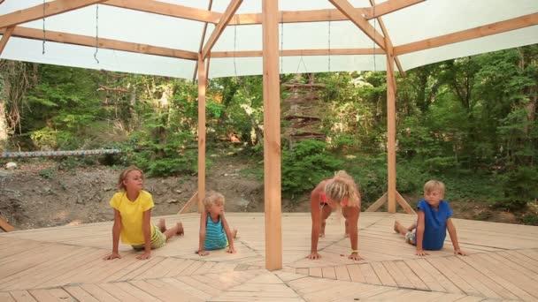 Děti různého věku, cvičení jógy s učitelem venku.