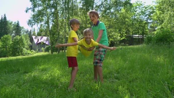 Šťastné děti hrají společně na zelené trávě na jaře parku. Koncept zdravého životního stylu. Starší bratři jsou kyvné z rukou svého mladšího bratra
