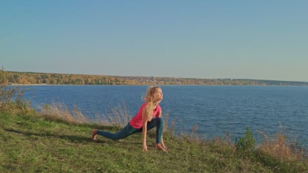 Young sportive woman doing exercises in autumn sunny day outdoors. Girl stretching her legs. Workout.