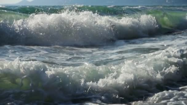 Slow motion. Big waves in black sea crashes over shore. Beautiful seascape in sunny day.