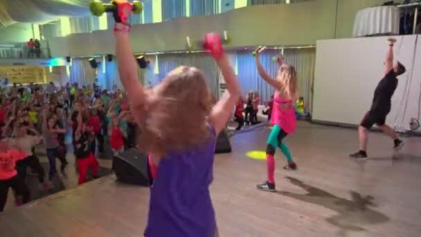 Novoszibirszk, Oroszország, március 18, 2018: fitness Fesztivál Zumba Marathon. A zenére és a tánccal kapcsolatos súlyzók mozgását bemutató oktatók.