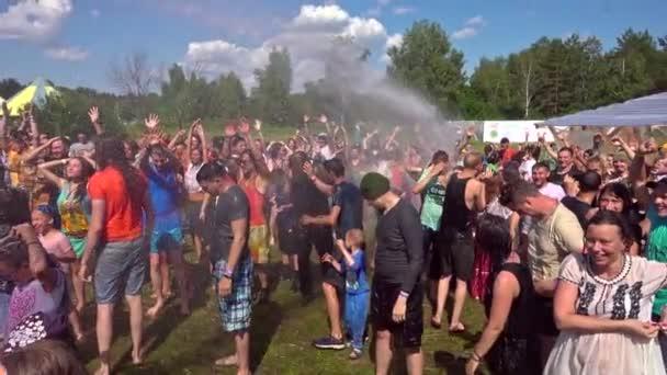 Barnaul, Rusko, 6. červenec 2019: Festival Jódského festivalu a Rawa. Šťastní vlhní lidé se baví a smějí se pod proudem vody s duhou.