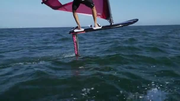 Handsome water sportsmen ride water surface. Windsurf and windfoil competition. Watersports competition. Vacation on seaside. Adventure summer.