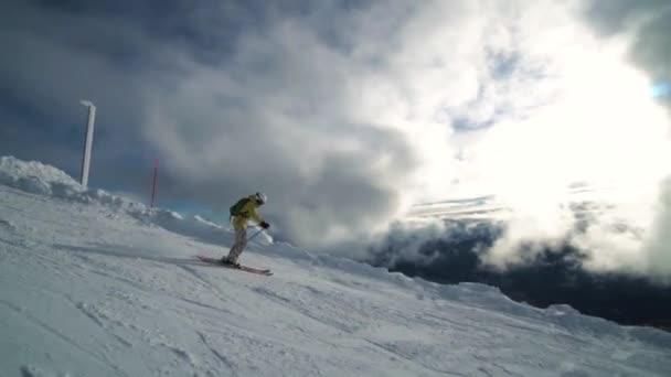 Zeitlupe einer Skirennläuferin, die vor faszinierenden Wolken durch den Gebirgsrand reitet.