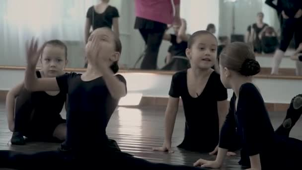 Little ballerinas dressed in blackl eotard are whispering and laughing during baby dance class. Kids have fun in dance class.