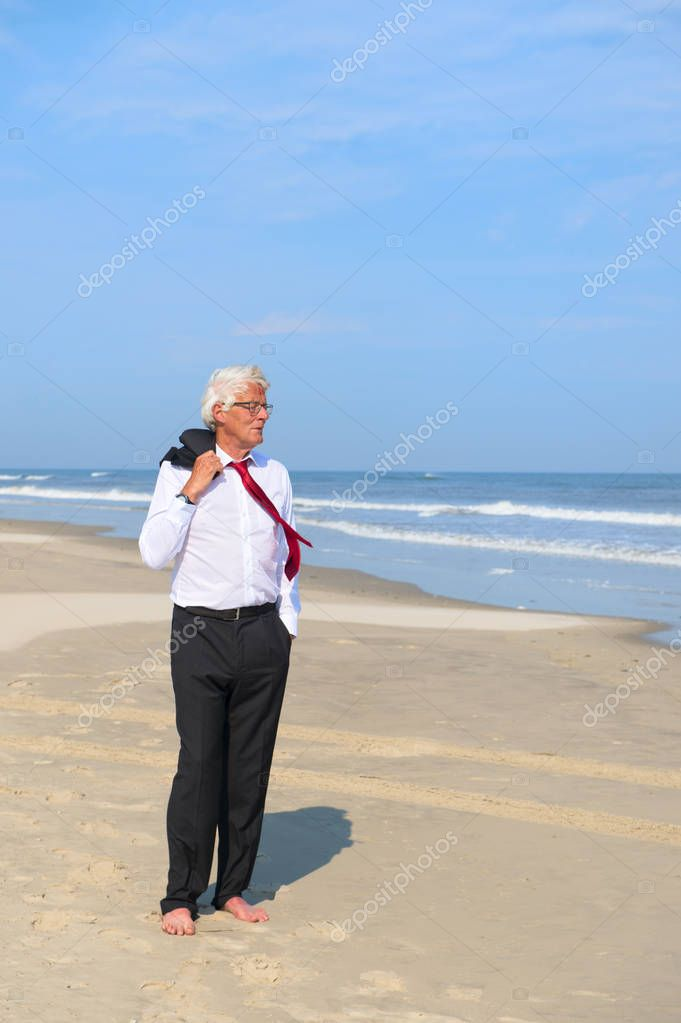 Business man in formal suit walking at the beach