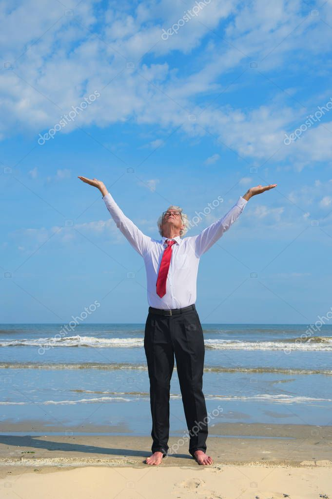 Business man in formal suit zen meditation at the beach