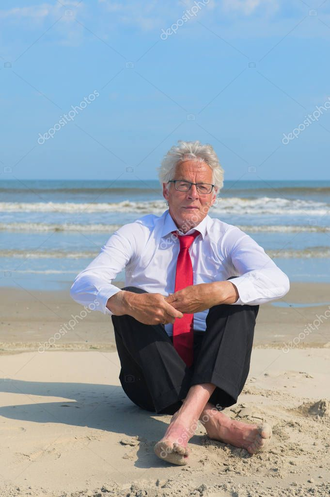 Business man in formal suit sitting at the beach