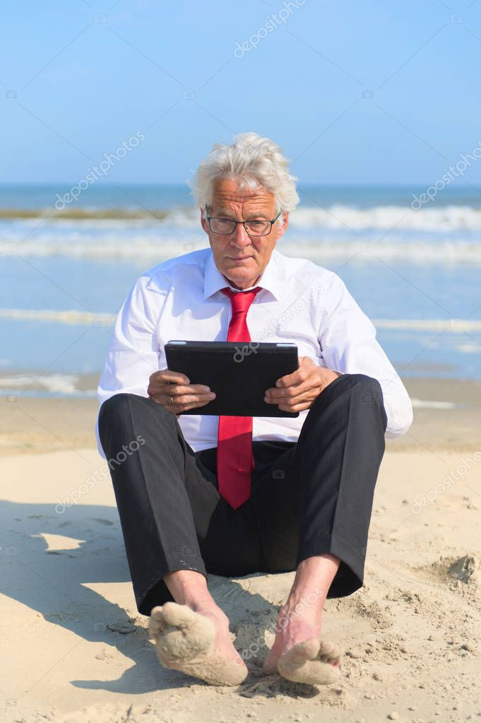 Business man in formal suit sitting and working with tablet at the beach