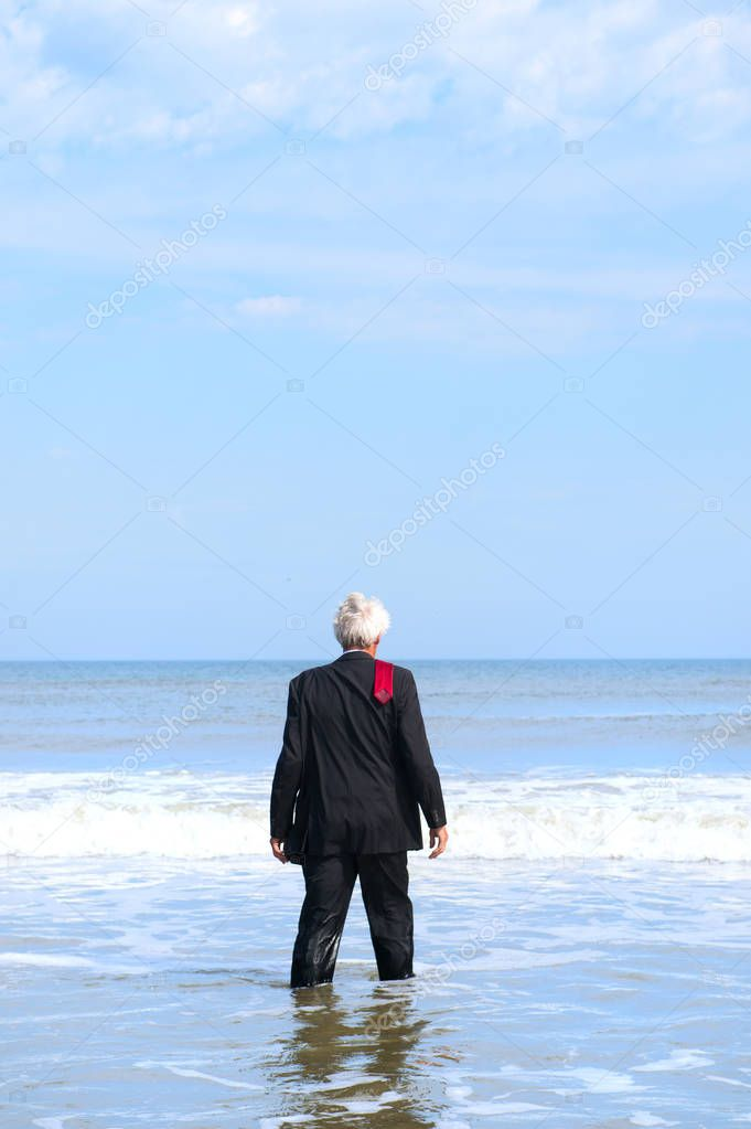 Business man in formal suit walking into the sea