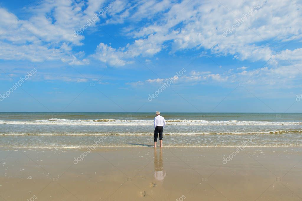 Business man in formal suit walking in the sea