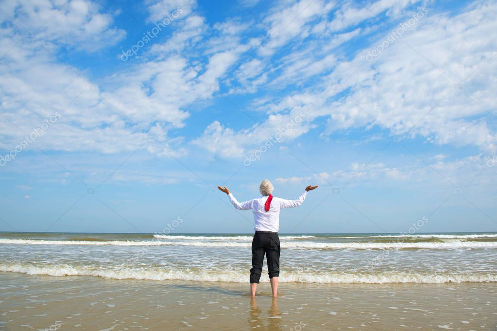 Business man gesturing to the sky, standing in the sea