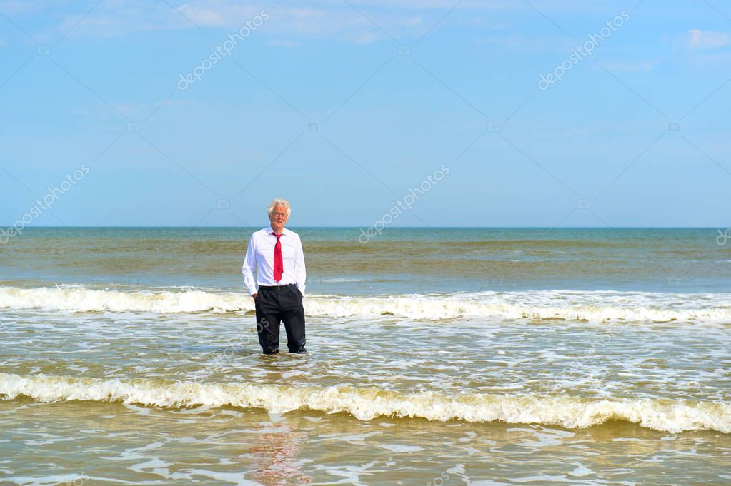 Business man in formal suit standing in the sea