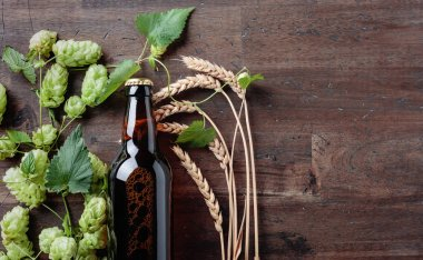 Bottle of beer, grain and hops on a old wooden background. Top view. Free space for text. stock vector