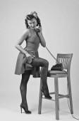 Fotografia Bella donna castana in stile parlando via telefono vintage pin up. Giovane donna attraente in 50s style con perfetto make-up e lacconciatura. Bianco e nero