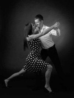 Young beautiful woman in polka dot dress and man in white shirt dancing tango. Couple in love dancing in the Studio. Black and white. stock vector