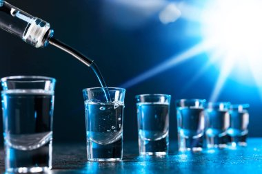 Vodka poured into a glass lit with blue backlight. Copy space. stock vector