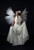 Nő fehér angyal jelmez szárnyakkal egy fekete háttér.