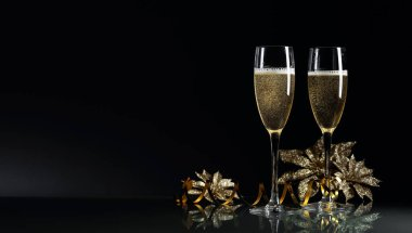 Two glasses of champagne ready to bring New Year on a black back